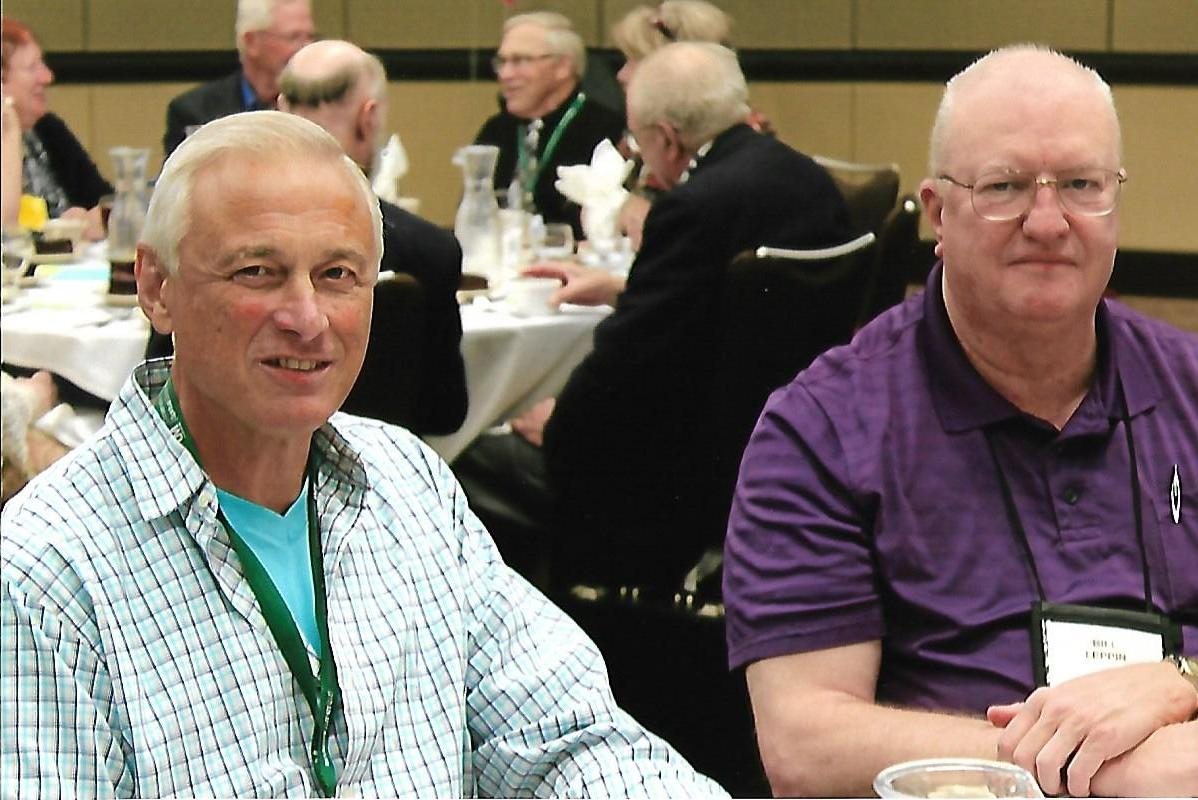 two men posing for a photo at a conference