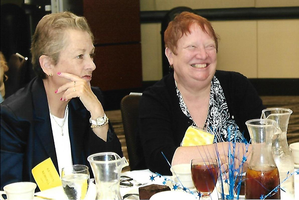 candid photo of two women laughing at a table at a conference