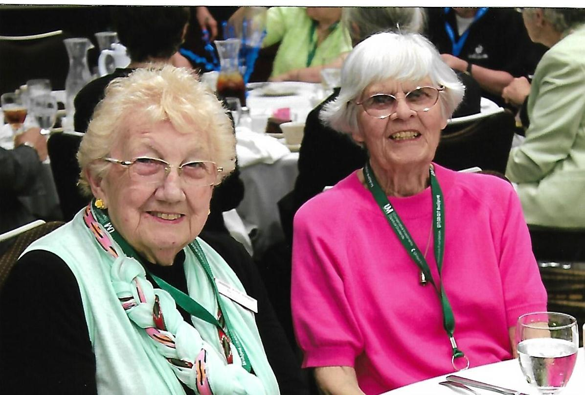 two women posing for a picture at a conference