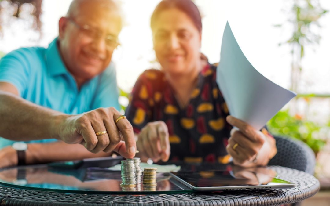couple sitting at a table making stacks with money coins